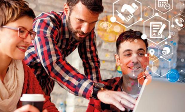 photo de personnes souriantes devant un ordinateur