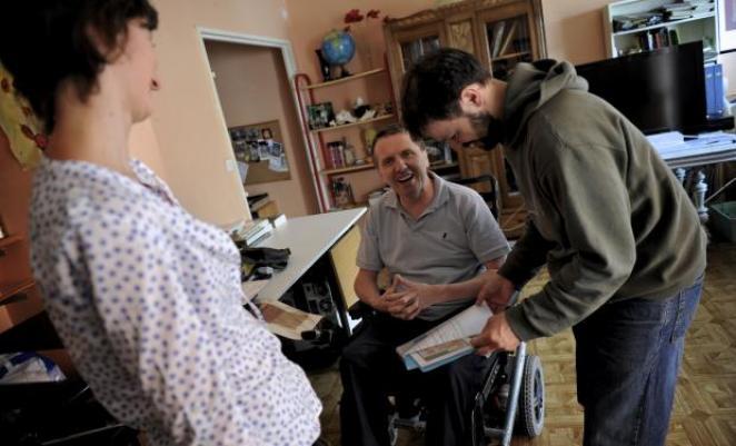 homme en fauteuil souriant accompagné de deux personnes